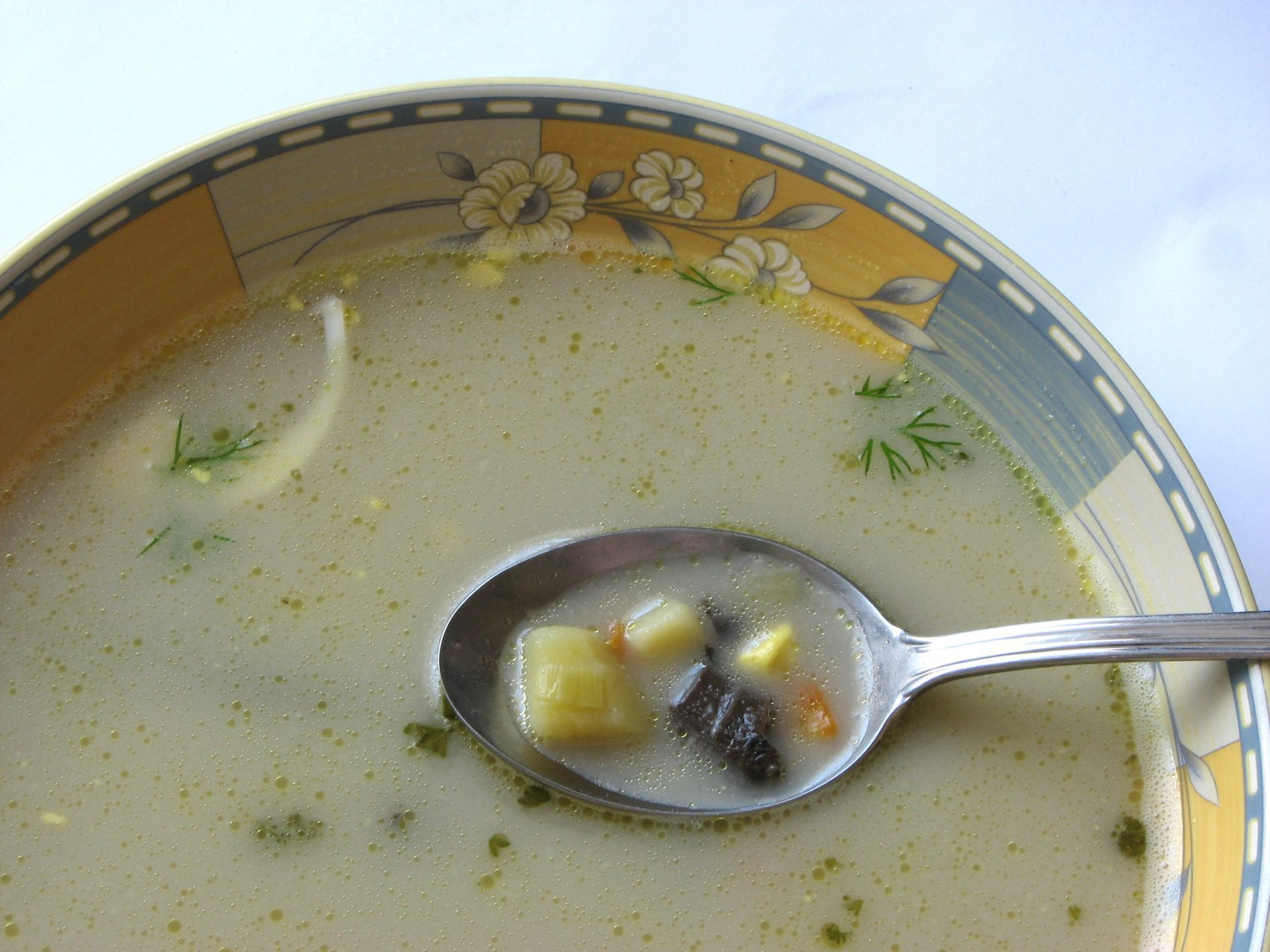 Close up of Rhode Island Clam Chowder with spoon in bowl
